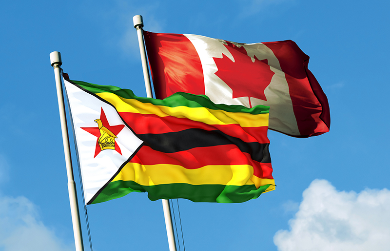 Flag of Zimbabwe waving together with the Canadian flag