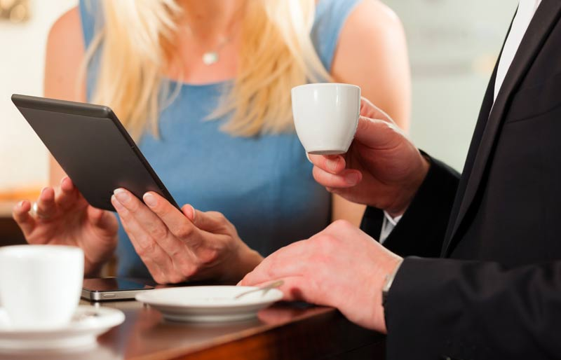 Two business people having a meeting: the woman is looking at a tablet, while the man is holding a mug.