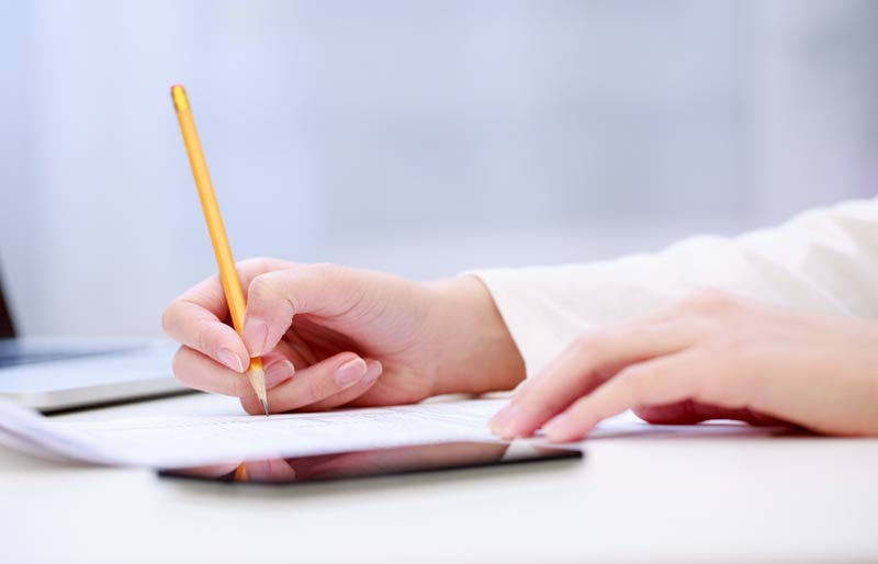 A close up of a hand writing an exam using a pencil.
