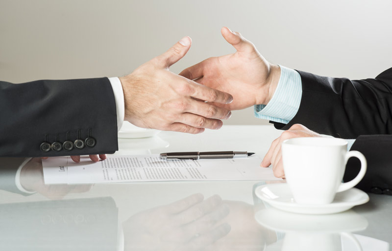 Business partners about to shake hands over contract