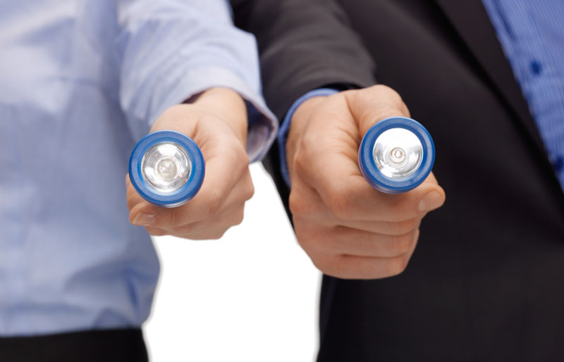 Man and woman holding flashlights side-by-side