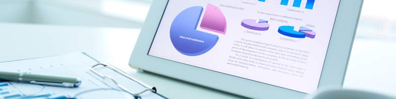 Tablet showing various pie charts and graphs in a dashboard view with glasses and a pen.