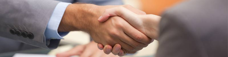 An image of two seated business professionals shaking hands.