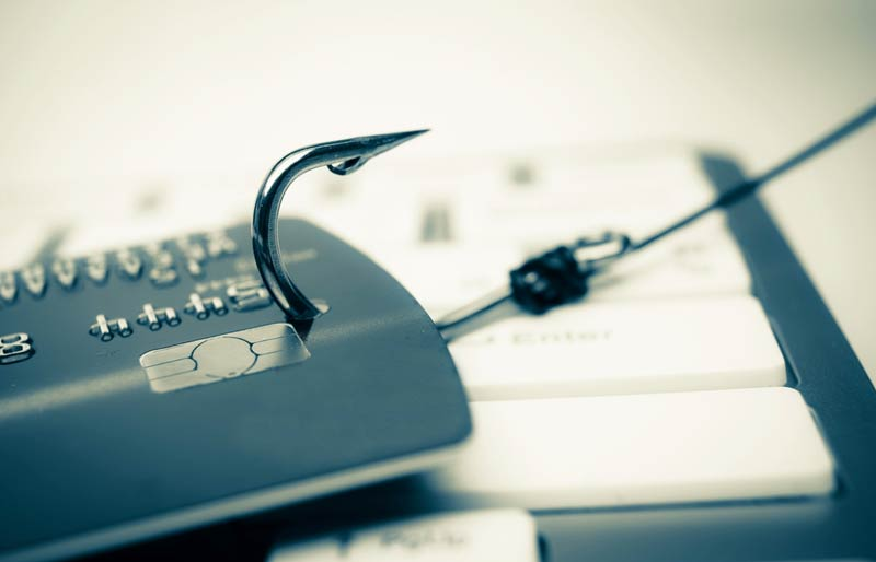 A close-up of a credit card that has been hooked by a fishing hook being dragged across a keyboard.