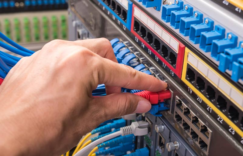 A close-up photograph of a IT professional plugging ethernet cable into a network server.