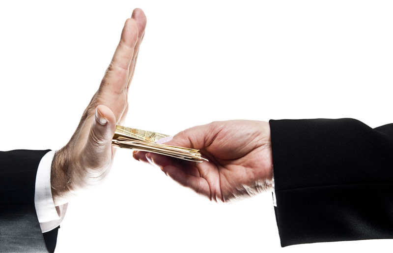 A closup-up crop of the hands of two business professionals, one handing over money the other not excepting.