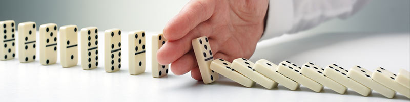 A businessman's hand i sstopping the dominoes from falling.