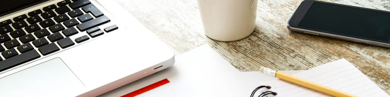 A close-up crop of a desk with a laptop, coffee, notepad and pencil and a mobile phone.