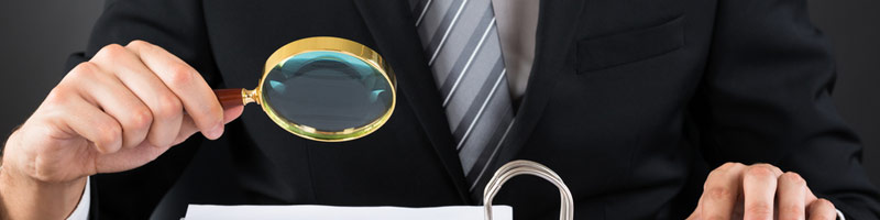 A close-up image of a business professional looking through a magnifying glass at some reports.