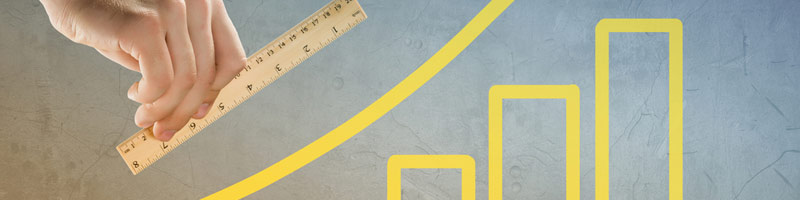 An conceptual image of a steadily increasing bar graph with an up-sweeping arrow and a male business professional measuring the increase with a wooden ruler.