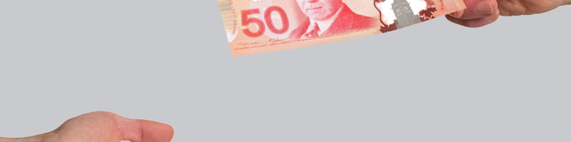 A close-up of one business professional handing a fifty dollar Canadian bill to another.