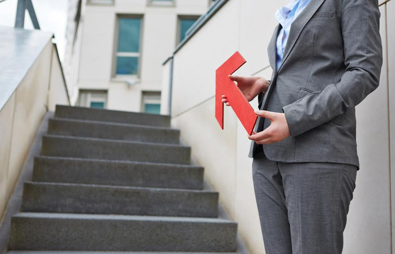A cropped image of a female business professional holding a large red arrow the points up a set of stairs.
