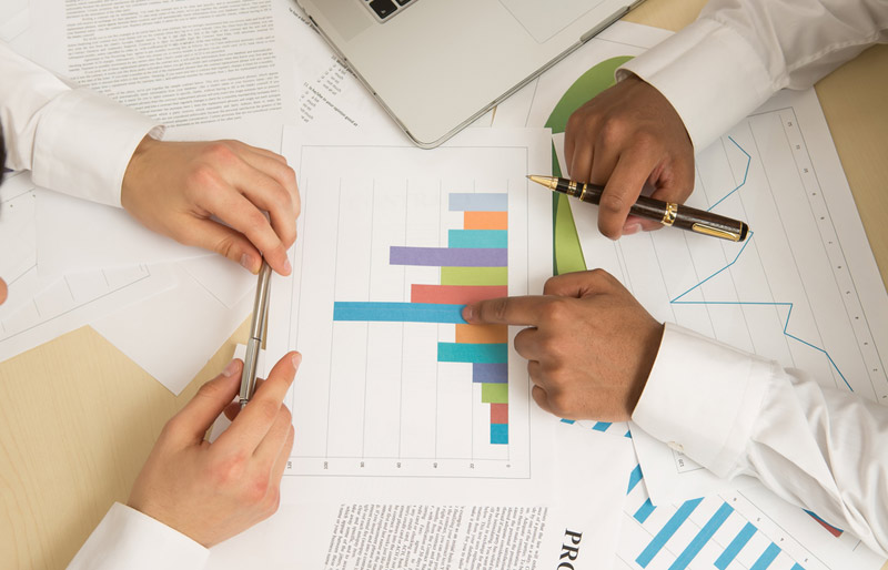 A close-up image of two business professionals at a desk reviewing various bar graphs.