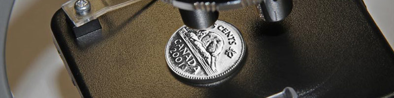 A close cropped image of a microscope with a Canadian Nickel on the platform.