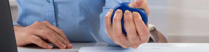 A business woman at her desk squeezing a stress ball.