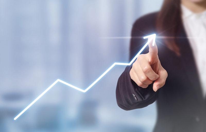 A businesswoman pointing at an increasing line graph