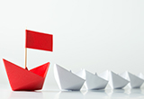 A red paper boat leading a row of smaller, white paper boats.