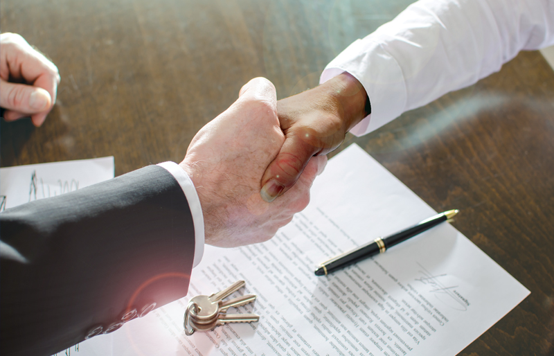 Business woman shaking the hand of another business person, over desk with a signed contract and keys