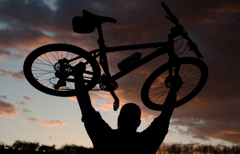 Silhouette of man holding up a bicycle against a backdrop of a sunset sky.