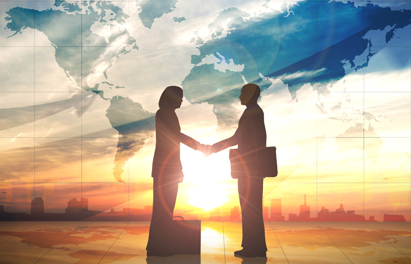 Silhouette of two business people shaking hands against a map of the world over a cityscape at sunset