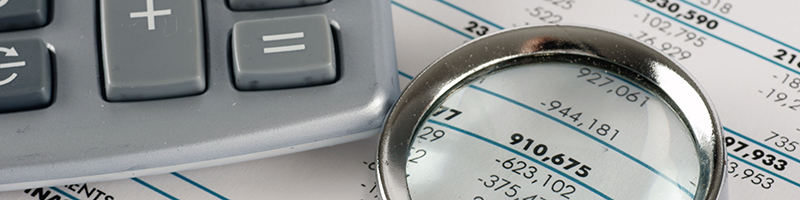 Close up of a magnifying glass and calculator on a business spread sheet of numbers