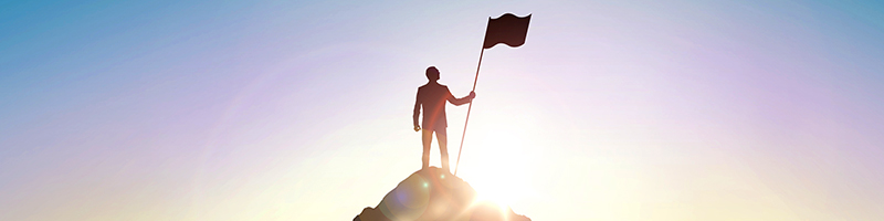 Person standing at top of hill with flag, against a sun rise sky