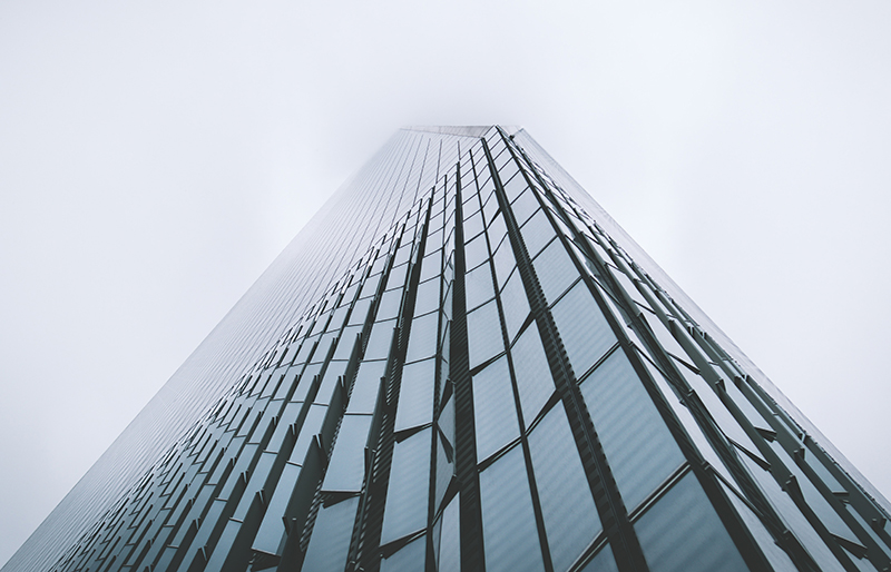 Worm's eye view looking up a modern glass skyscraper against grey foggy sky