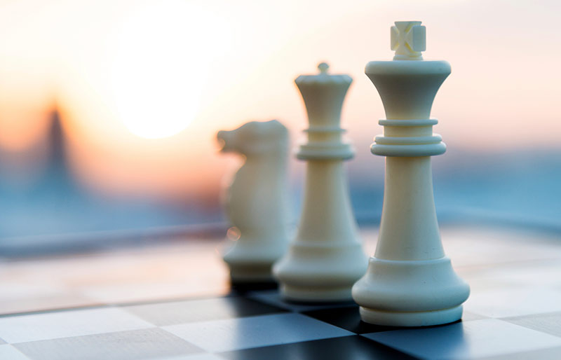 Three white pieces of a chess set on a chessboard, on background sunset.