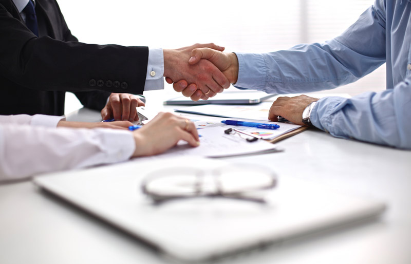 An photo of a male and female business professional shaking the hand of a job applicant.