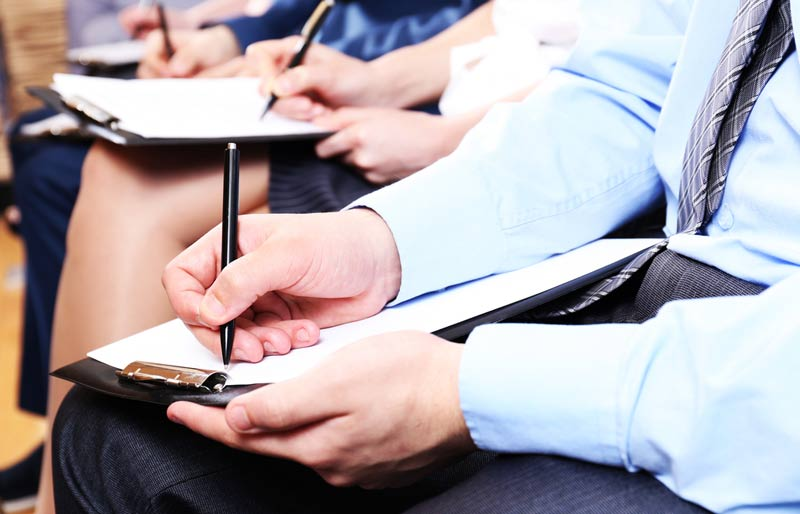 Business professional hands holding pens and making notes at conference.