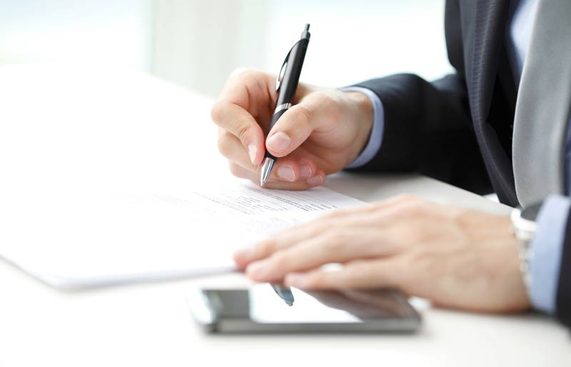 Close-up of businessman sitting at office and fill the form.