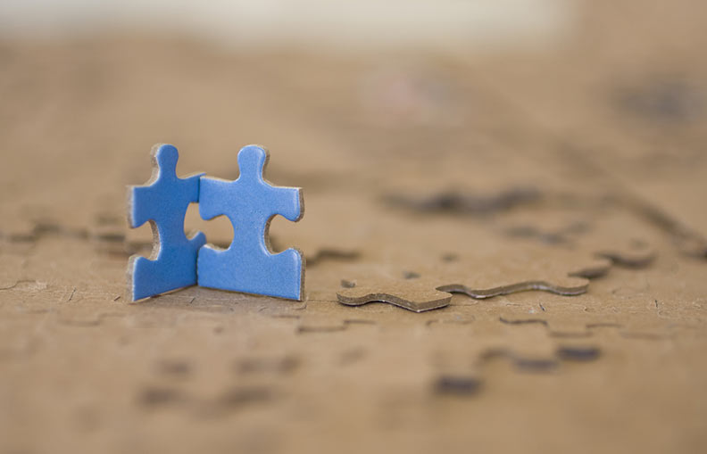 Two blue puzzle pieces in the form of figures that stand by the hand