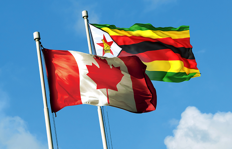 Canadian and Zimbabwe flag waving together