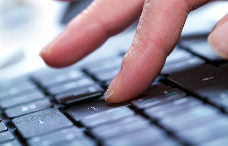 Close up of a businessperson's hand typing on a laptop keyboard