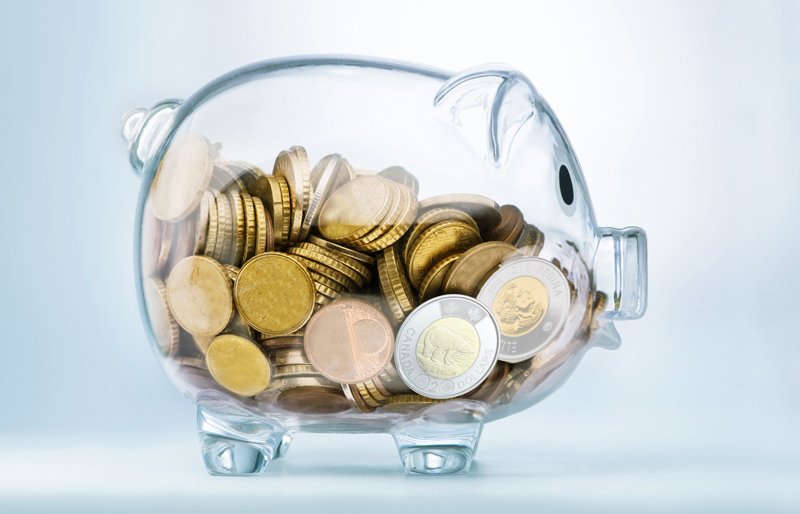 A clear glass piggy bank filled with coins.