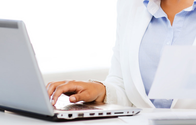 A close crop photo of a female business professional working at her desk on a laptop.