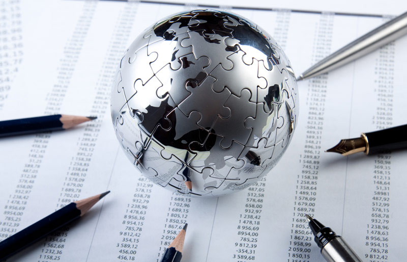 Globe made of puzzle pieces sitting on paper financial statement with pencils and pens pointing at globe