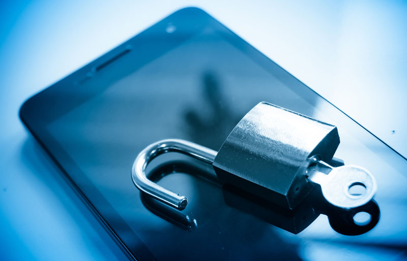 A close-up image of an iPhone with an open padlock with a key inserted resting on the screen.