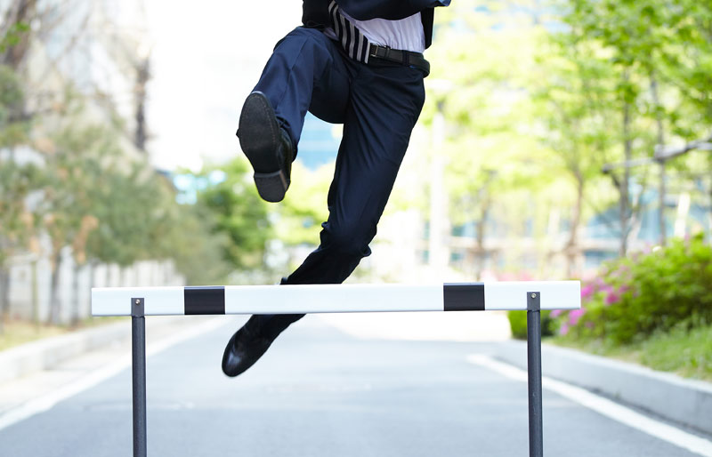 Businessman in suit jumping racing hurdle on quiet street
