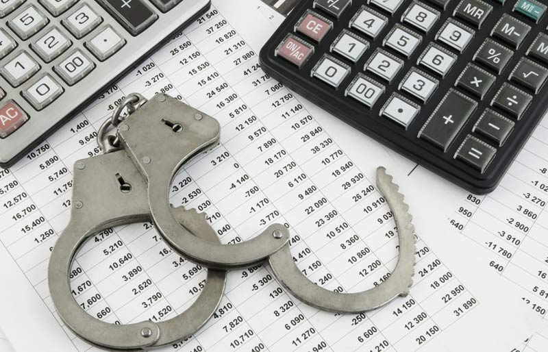 Calculator and a pair of open handcuffs sitting on an accounting spreadsheet.