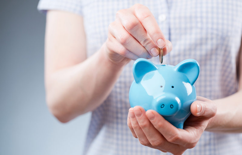 A close-up image of a female in a short sleeved shirt placing a coin into a blue piggy bank.