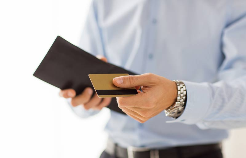A business professiona holding an open wallet and presenting a gold rewards card.