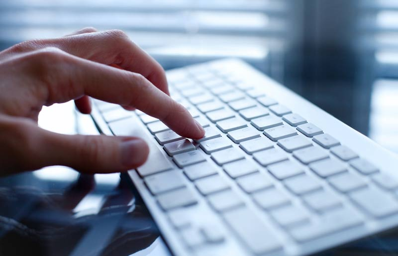 An image of a male business professional typing on a keyboard.