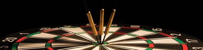 A cropped image of a dart board laying on a table with three darts sticking in the bullseye.