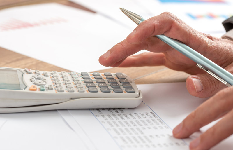 A close-up of a business professional holding a pen and working on a calculator and spread sheets.