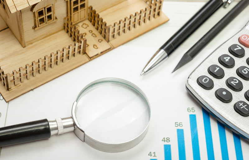 An image collage showing a magnifying glass, pen, pencil, calculator and a model house sitting on a bar graph.