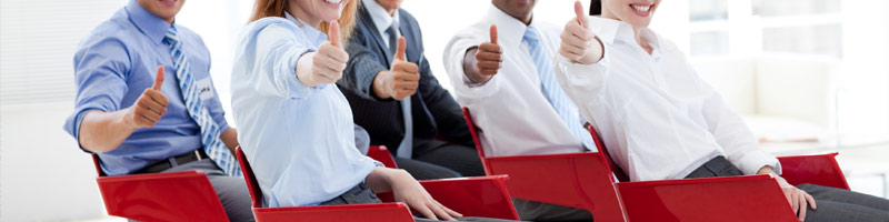 Business people with thumbs up at a presentation