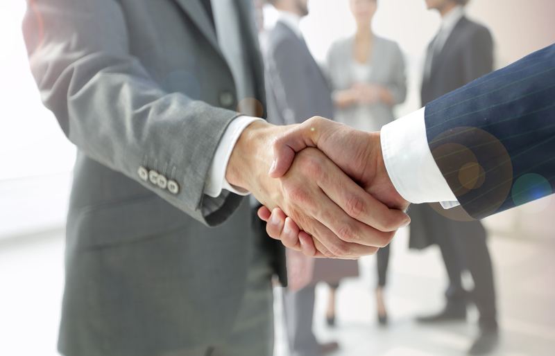 Two businessmen shake hands, with group of shareholders in the background