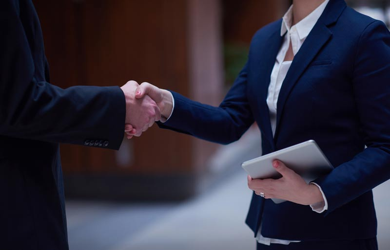 A photograph of a female and male business professional shaking hands.