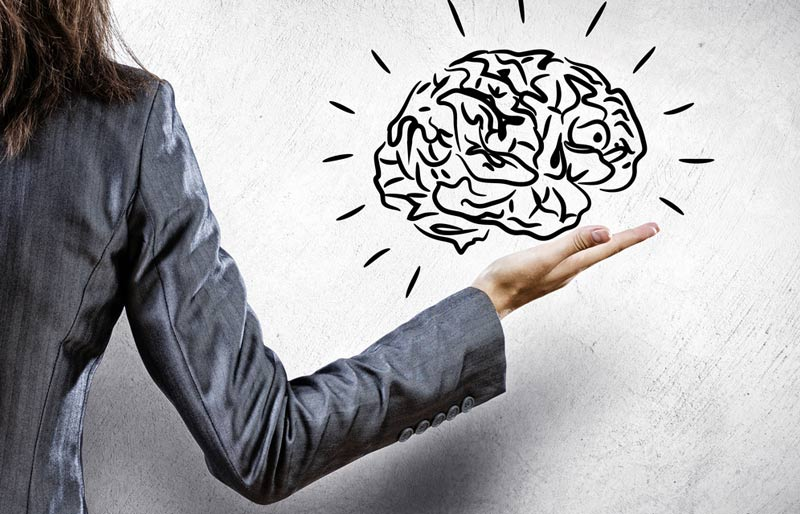business woman holding sketch of a brain in one hand